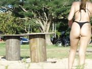 Woman with a great big thick ass wearing thong is filmed at the beach